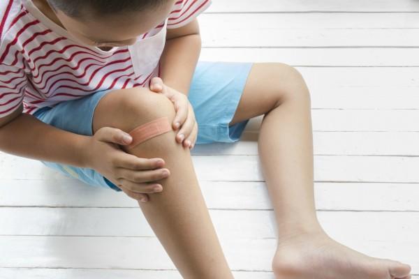Criança com curativo no joelho