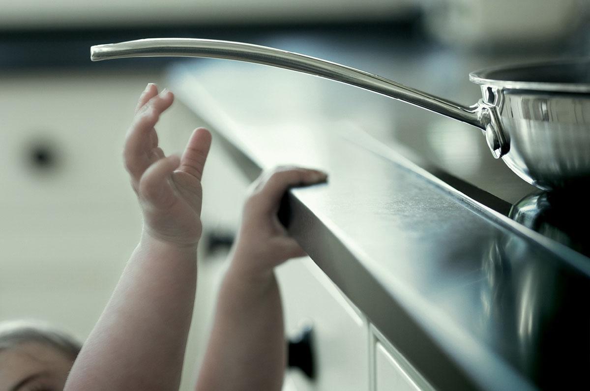Criança tentando pegar uma frigideira