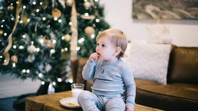 Criança sentada na mesa comenda cookies